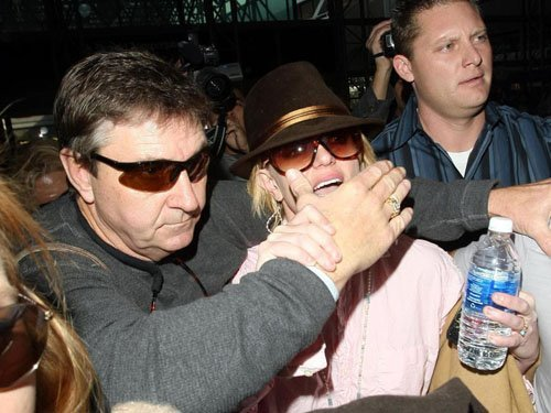 RESTRICTIONS APPLY: No smiling! Britney Spears muzzled by overprotective dad Jamie as she leaves LA for her European tour
