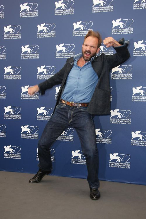 """Ralph Fiennes dances at the photo call for the film, """"A Bigger Splash,"""" during the 72nd edition of the Venice Film Festival in Venice, Italy, Sunday, Sept. 6, 2015. (Photo by Joel Ryan/Invision/AP)"""