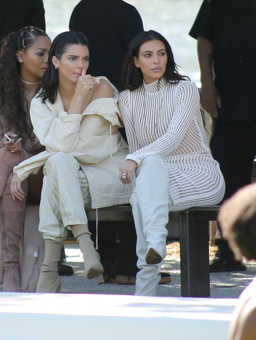 Kim Kardashian and Kendall Jenner watch the Yeezy season 4 show in a park with other celebs and sisters as they watch the runway models